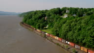 WIDE AERIAL POV past train on tracks along Hudson River in rural area