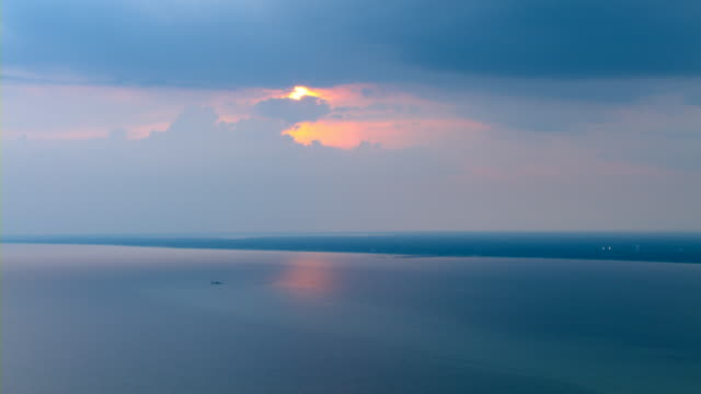 Pastel clouds glow above the calm waters of the Gulf of Mexico at golden hour.