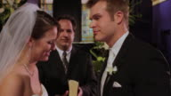 CU of pastor; PULL as bride and groom kiss, then walk toward camera