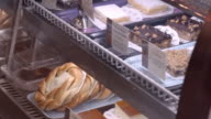 PAN pastries under curve tempered glass in bakery display case and sugar coated cookie lifted by pastry tong / Redlands, California, USA