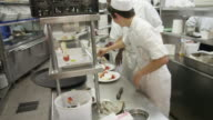 POV pastry chef and helpers working in the cold plating area of a restaurant kitchen