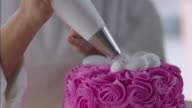 Pastry chef decorates pink cake with white icing designs