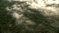 Patchy clouds hang above the Amazon Rainforest near the Amazon River. Available in HD.