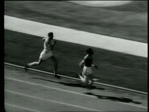 Pathe News title card 5000 Meter Run / Won by Lehtinen Finland No 125 Time 14 30 / Wide pan of runners on the track from starting line around the...