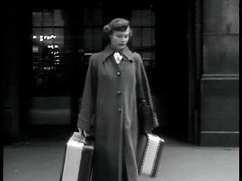 DRAMATIZATION 'Patricia Cugarman' walking out of Grand Central Station carrying suitcases looking up at buildings female gloved hands checking money...