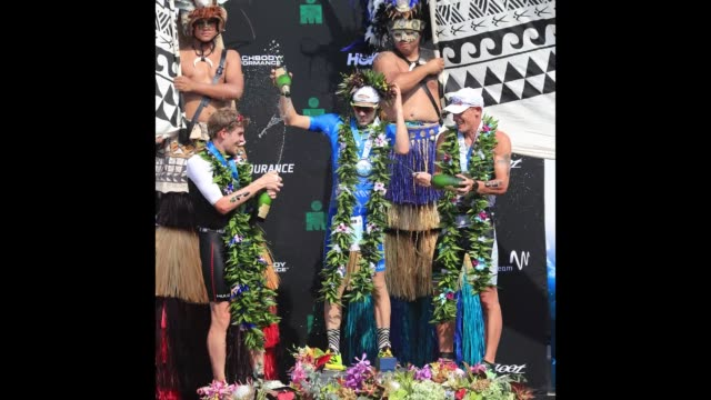 Patrick Lange of Germany celebrates after winning the IRONMAN World Championship along with David McNamee of Great Britain who finished third and...