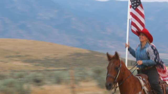 Patriottische Cowgirl berijden van een paard met een Amerikaanse vlag