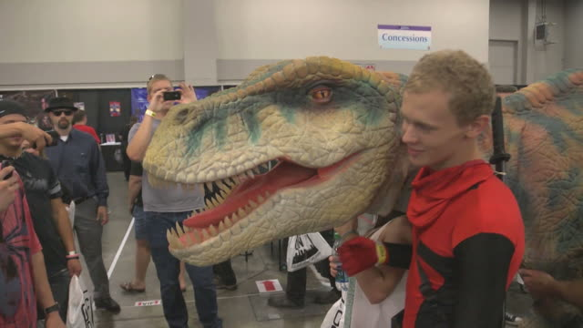 Patron of the first annual Comic Con is Salt Lake City Utah poses with a large dinosaur