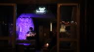 Patrons listen as a musician performs at a Lake Houhai bar.
