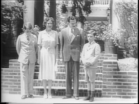 Pawling NY sign / Thomas Dewey walks down the steps of his home with his Frances and children Thomas Jr and John / Dewey brushes his son John's hair...