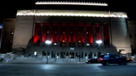 Peabody Opera House w/ facade illuminated in red across Market Street as cars park at curb light traffic passes by in FG