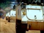 UN APC peacekeeping vehicles pass along dusty road eastern Democratic Republic of Congo