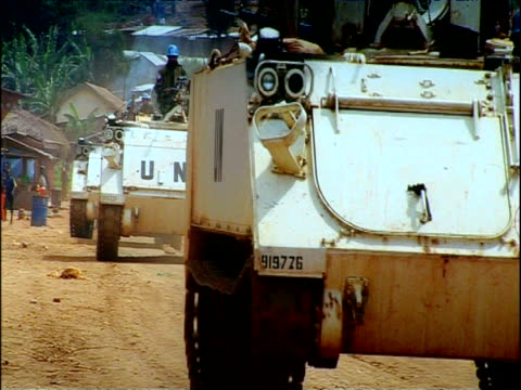 UN APC peacekeeping vehicles pass along dusty road eastern Democratic Republic of Congo