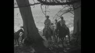 'Pebble Beach Calif' superimposed over women horseback riding / VS women ride horses through seaside forest / VS women on horseback fire arrows from...