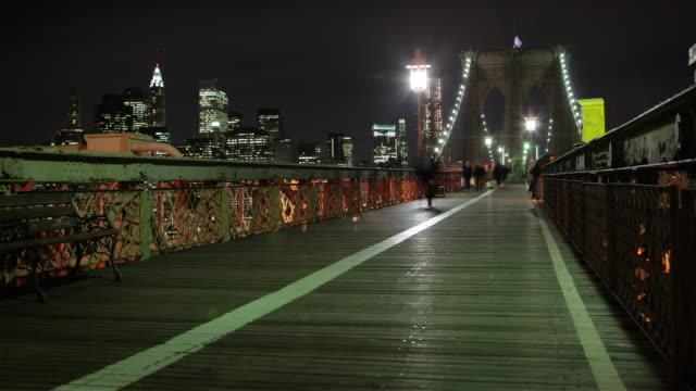 WS T/L Pedestrian and bicycle traffic on Brooklyn Bridge in New York City at night, Manhattan skyscrapers in background / New York City, New York, USA