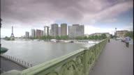 A pedestrian bridge crosses the Seine River as traffic passes below.