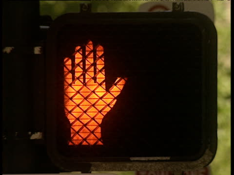 Pedestrian crossing with red hand flashing then constant signaling don't walk