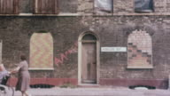 1980 MONTAGE Pedestrian pushing wheelchair patient past boarded-up building and family exiting building and walking down the street / United Kingdom