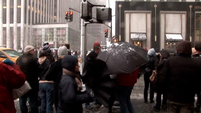 Pedestrian wait to cross road in high winds during a snowstorm Manhattan
