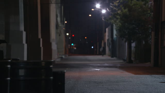 WS Pedestrian walking on far side of a empty alleyway / United States