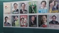 A pedestrian walks past posters of South Korean presidential candidates in Incheon South Korea on Monday May 8 Moon Jaein presidential candidate of...