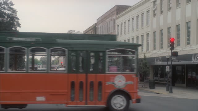MS Pedestrians and car traffic, including a trolley car, passing through city intersection / Tybee Island, Georgia, United States