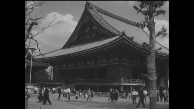 Pedestrians and faithful Buddhists walk beside Senso-ji.