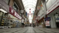 Pedestrians and shoppers walk through a shopping arcade in Tokyo Japan on Friday July 25 A sale price sign is displayed outside a store An elderly...