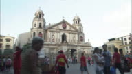 Pedestrians and street vendors crowd a plaza in front of a church.