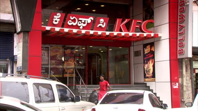 Pedestrians and traffic pass by a KFC.