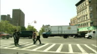 Pedestrians and traffic pass through a New York City intersection. Available in HD.