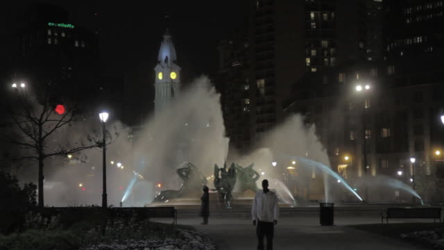 WS Pedestrians and traffic passing Swann Memorial Fountain at night, with City Hall clock tower in the distance / Philadelphia, Pennsylvania, United States
