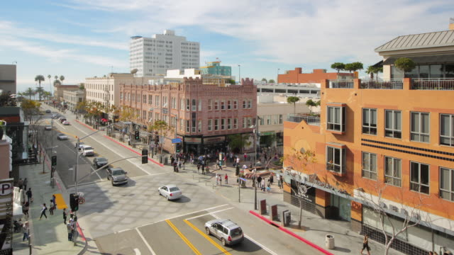 Pedestrians and traffic rush across Third Street Promenade in Santa Monica, California.