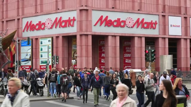 Pedestrians carry shopping bags in Berlin Germany on Tuesday May 26 2015 Shots pedestrians pass by a Media Markt retail store at Alexanderplatz...