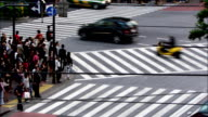 Pedestrians cross a busy intersection after traffic comes to a stop. Available in HD.