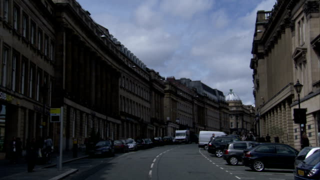 Pedestrians cross a Grey Street, lined with Victorian buildings, in Newcastle upon Tyne. Available in HD.