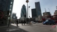 Pedestrians cross the street backdropped by 30 St Mary Axe also known as the Gherkin in London on Monday May 11 2015 SHOTS a businessman stands with...