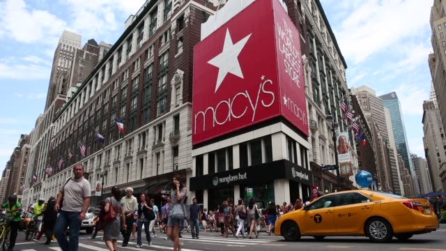 Pedestrians cross the street in front of the Macys Inc flagship store in New York US