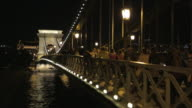 Pedestrians cross the Széchenyi Chain Bridge at night