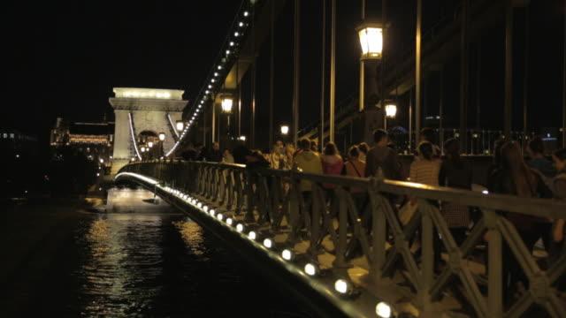 Pedestrians cross the Széchenyi Chain Bridge at night
