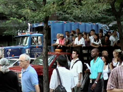 Pedestrians crossing street near truck crowded with passengers during citywide blackout on August 14 2003 / New York New York USA / AUDIO