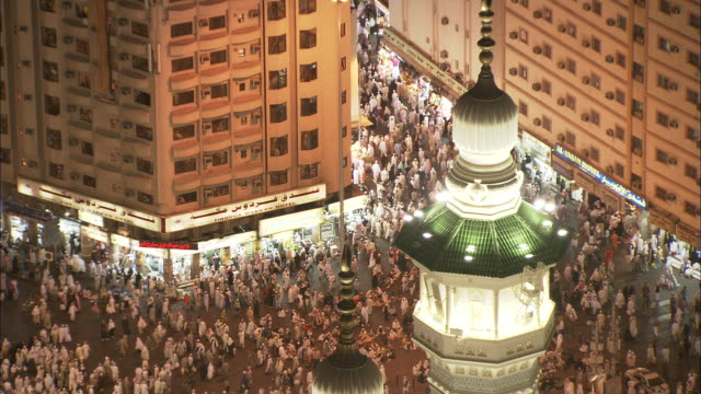 Pedestrians crowd streets in a Saudi Arabian city.