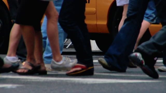 Pedestrians' legs walk on a crosswalk in New York City.