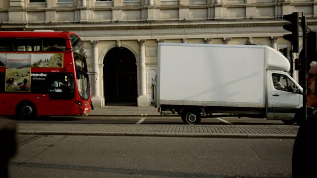 Pedestrians, London red buses and souvenier shop at Trafalgar square