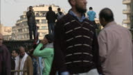 Pedestrians milling through Tahrir Square some standing on barricades while others are on balconies of buildings / Cairo Egypt
