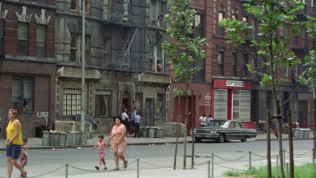 1969 WS PAN ZI Pedestrians on sidewalk and people standing outside apartment building/ Brooklyn, New York, USA