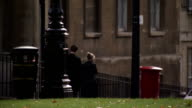 Pedestrians pass a postbox in Queen Square in Bath. Available in HD.