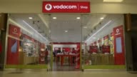 Pedestrians pass a Vodacom Group Ltd mobile phone store in the Rosebank Mall in Johannesburg South Africa on Wednesday March 25 2015