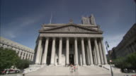 Pedestrians pass by the New York Supreme Court building.