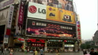 Pedestrians pass huge digital billboards, China. Available in HD.